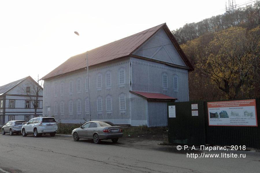 Дом в саркофаге (улица Красинцев, 13). Справа — забор, установленный вокруг дома № 15, с охранной доской и планом реставрации.